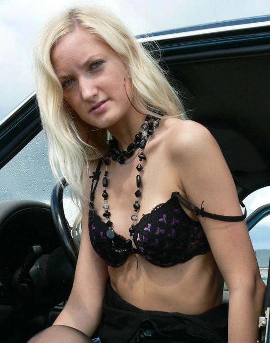Сногсшибательная русская девушка в сексуальных черных чулках возле авто позирует